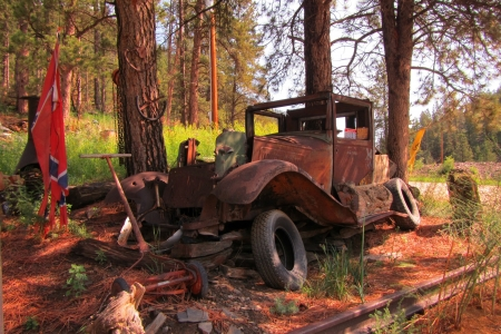 Old rusted out vehicle on the bend of a dirt road in South Dakota