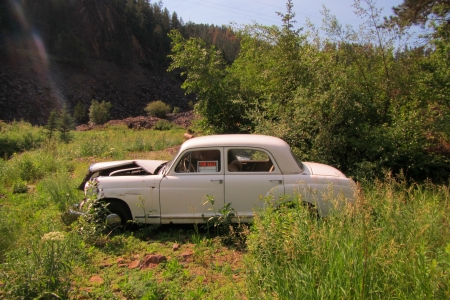 Old abandoned car in ditch with a for sale sign in the window  Banco de Imagens