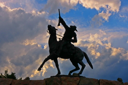 cody: Dramatic shilouette of Buffalo Bill Cody set against dramatic clouds near sunset