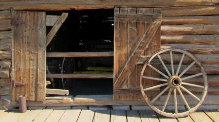 Beautiful old wagon wheel proped against a log barn  Stok Fotoğraf