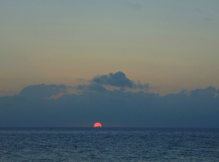 First glimspe of the sun rising over the Carribean Sea  photo