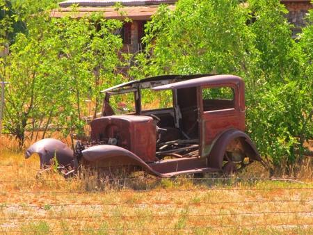 Old rusty car in field