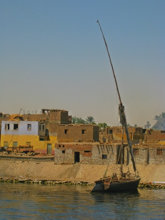 nile river: Nile river bank with old mud brick buildings and felluca style fishing boat Stock Photo