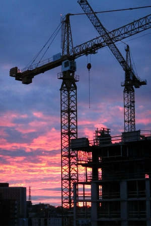 Construction cranes with beautiful sunset in the background
