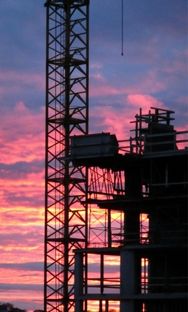 subcontractors: Construction crane close up with beautiful sunset in the background