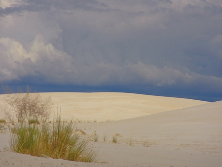 unpredictable: Dark sky contrasting with white sand of the dunes Stock Photo