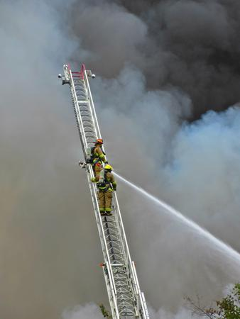 Firefighters on aerial ladder surrounded by smoke. Редакционное