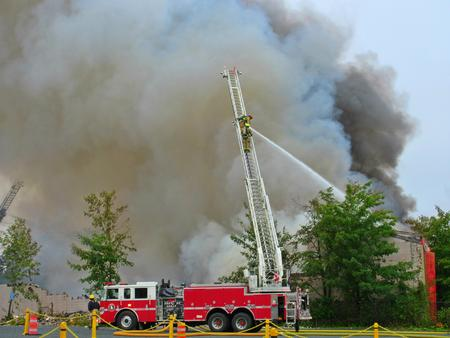 Fire truck with aerial ladder deployed engaging fire.