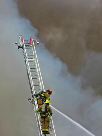 Two firefighters on the aerial ladder fighting fire from above. Editorial