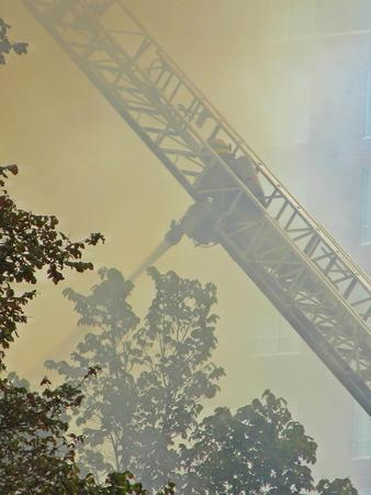 heros: Firefighter enshrouded by smoke while fighting fire.