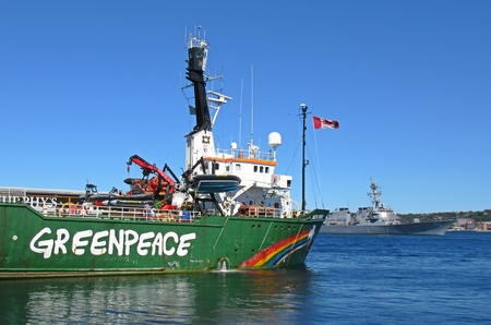 Greenpeace ship docked in Halifax as Canadian Frigate passes by on way to participate in NATO antisubmarine warfare exercises off Canada's east coast.