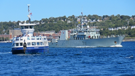 Halifax passenger ferry stops for naval ship in Halifax Nova Scotia harbor as it departs into the Atlantic coast during NATO exercises.