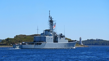Canadian naval frigate departs Halifax Nova Scotia harbor with McNabs Island lighthouse in the background.