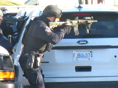 Police SWAT team officer aims weapon. Editorial