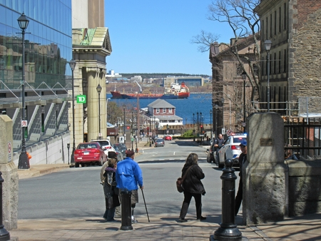 Looking down a Halifax Nova Scotia street with a view of the harbor and a ship in the background.