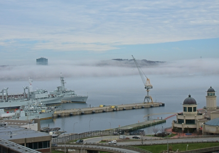 Foggy Halifax harbor with view of Dartmouth skyline obscured by fog. In the foreground can be seen naval ships and the Casino Nova Scotia.