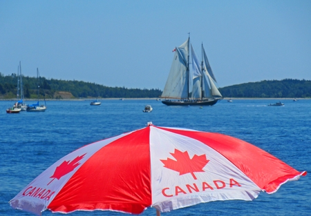 Famous Bluenose Schooner with Canadian flag umbrella in the foreground in Halifax harbor during the Tall Ships Festival 2017.