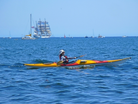 Kayaker in Halifax Nova Scotia with American Coast Guard sailing ship the Eagle on the horizon. Editorial