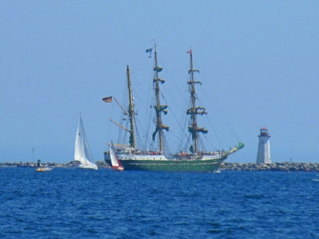 Tall ship with McNabs Island Lighthouse in the background.