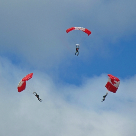 Three Canadian Forces Military Skyhawks members under Canadian Flag parachutes.