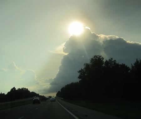 Sun peaking over storm cloud. Banco de Imagens - 87389289