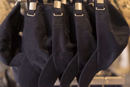 sported: Dark Blue Baseball Hats hanging In A Row