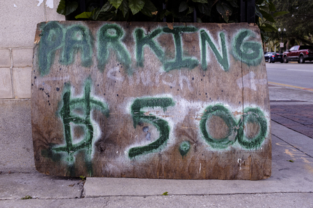 A Sign That Reads Parking Five Dollars In Green And White