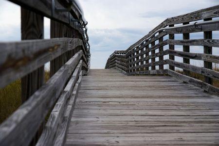 fenced boardwalk under open sky photo