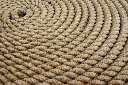 Thick rope coiled flat on ground      photo