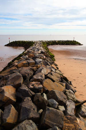 A row of sea defence boulders jutting out into the water