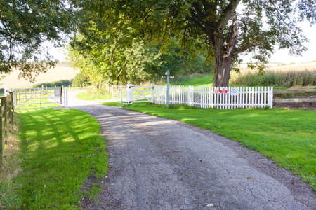 White picket fence alongside a country lane with an open gate