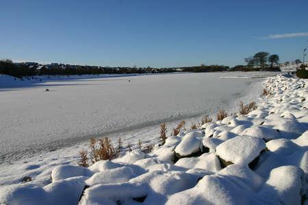 Looking across a frozen loch in the James Hamilton Heritage Park in East Kilbride, South Lanarkshire, Scotland.