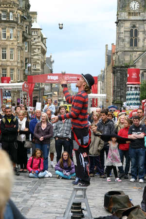 Edinburgh, Scotland, UK - September 18, 2011: Street entertainer juggling silver metal balls while standing on a small step ladder.