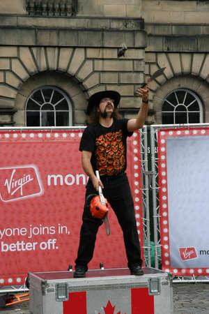 Edinburgh, Scotland, UK - September 18, 2011: Street entertainer juggling a chain saw, a hand grenade and a dagger at the Edinburgh Festival.