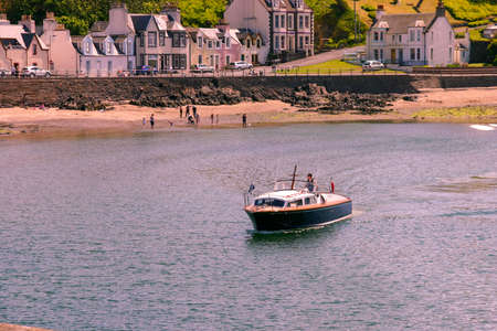 Portpatrick, Dumfries and Galloway, Scotland, UK - May 27, 2012: Boat arriving in Portpatrick, Scotland on a sunny day.