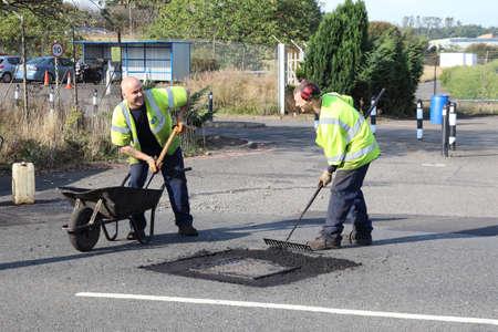 East Kilbride, South Lanarkshire, Scotland, UK - September 08, 2014: Two workmen enjoying their work in the sun.