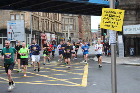 Glasgow, Scotland, UK - June 21, 2015: Image showing a parking sign and runners competing in the Glasgow mens 10K run running along Saltmarket.