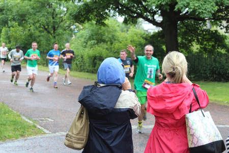 Glasgow, Scotland, UK - June 21, 2015: Spectators watching runners at Glasgow Green during the Glasgow 10K 2015.
