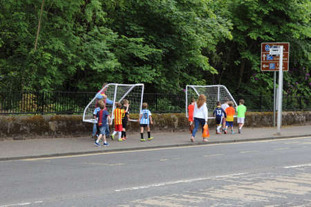 Glasgow, Scotland, UK - June 20, 2015: A group of children and adults taking some goalposts to the local park for a game of football. Editorial