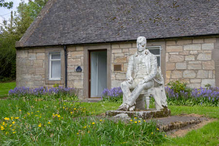 East Kilbride, South Lanarkshire, Scotland, UK - May 13, 2019: Sir Walter Scott statue outside an old cottage in East Kilbride, South Lanarkshire, Scotland, UK. Editorial