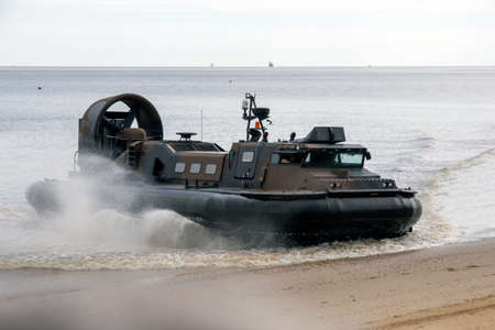 Cleethorpes, North East Lincolnshire, England, UK - June 25, 2016: Military Hovercraft coming ashore on a sandy beach during Cleethorpes armed forces day.