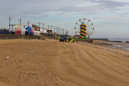Cleethorpes, North East Lincolnshire, England, UK - August 18, 2020: Cleethorpes beach looking towards the small funfair and showing a tractor being used to clean the sand.