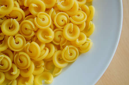 mediteranean: A plate of uncooked dried Dischi Volanti pasta in natural sunlight. For a healthy lifestyle, diet and sports nutrition