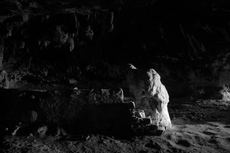 White illuminated rock in dark spooky cave Фото со стока