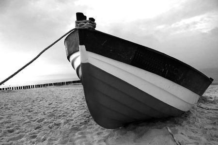Old fishboat on sandy beach. Beautiful sunset - Baltic Sea in Poland Stock Photo
