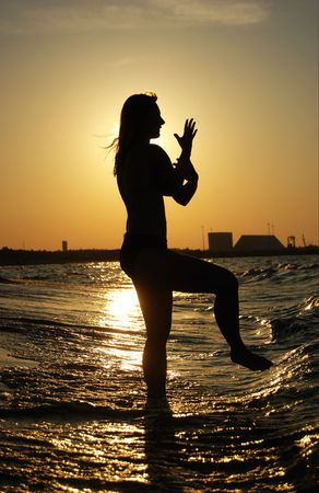 Beautiful girl practising Tai Chi on a beach. photo