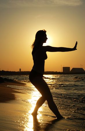 Beautiful girl practising Tai Chi on a beach. Stock Photo