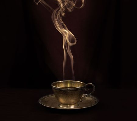 Hot coffee in gold antique cup, and smoke above