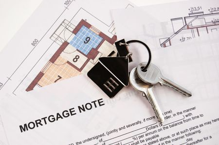 Keys on mortgage note and blueprints Stock Photo