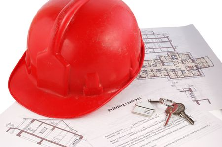 Keys and helmet on building contract and blueprints photo